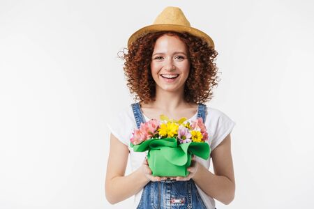 Portrait of feminine redhead curly woman 20s wearing summer straw hat smiling and holding flower box isolated over white background