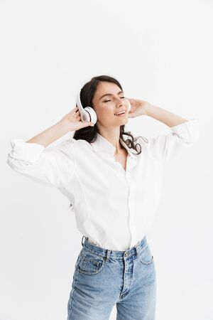 Cheerful young brunette woman wearing shirt standing isolated over white background, listening to music with headphones Stock Photo