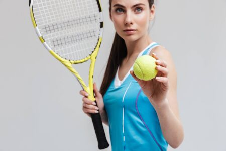 Cropped image of a confident woman tennis player holding racket and ball isolated over gray background Stock Photo