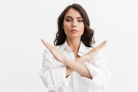 Beautiful angry young woman with long curly brunette hair wearing white shirt standing isolated over white background, showing stop gesture 写真素材
