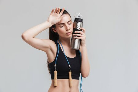 Image of a beautiful young tired sport fitness woman posing with skipping rope isolated over grey wall background holding bottle with water.