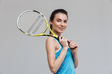 Image of a beautiful young sport fitness woman tennis player make exercises isolated over grey wall background. Stock fotó