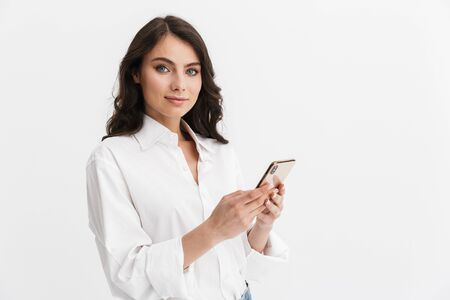Beautiful smiling young woman with long curly brunette hair wearing white shirt standing isolated over white background, using mobile phone Imagens