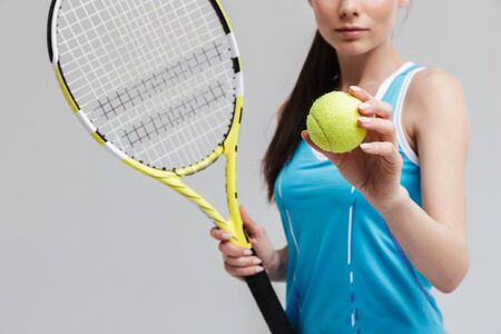Cropped image of a confident woman tennis player holding racket and ball isolated over gray background Imagens