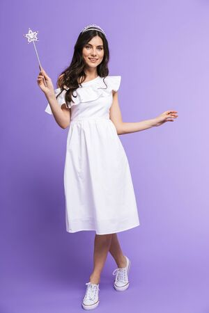 Full length of a beautiful young brunette woman wearing dress and diadem with magic wand isolated over violet background