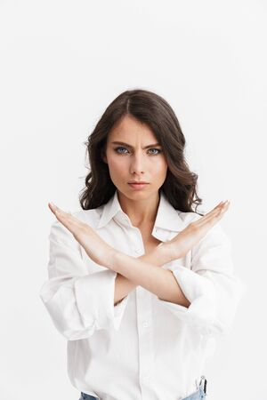 Beautiful angry young woman with long curly brunette hair wearing white shirt standing isolated over white background, showing stop gesture Stock Photo