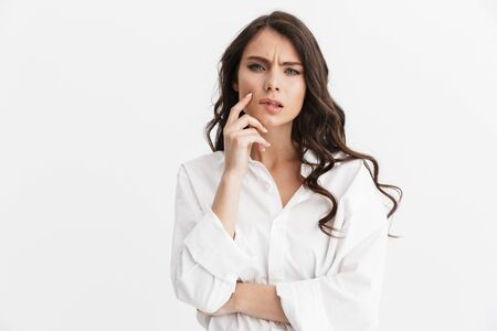 Beautiful pensive young woman with long curly brunette hair wearing white shirt standing isolated over white background