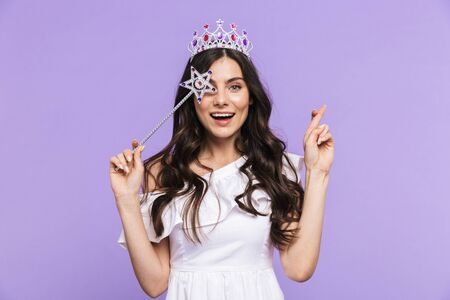 Beautiful lovely young woman wearing princess outfit standing isolated over violet background, posing with magical wand