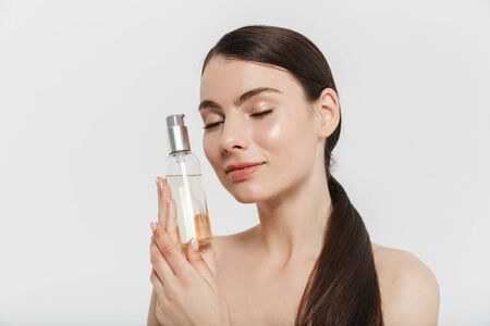 Beauty portrait of an attractive young brunette woman standing isolated over white background, showing bottle with facial oil