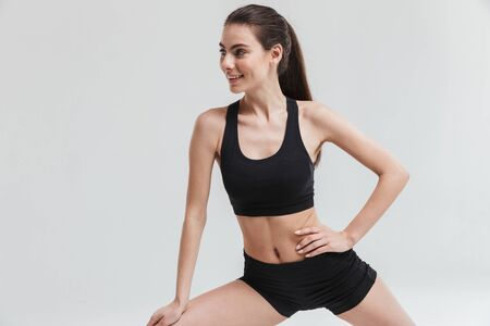 Image of a beautiful young sport fitness woman make exercises isolated over grey wall background.