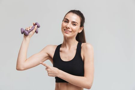Image d'une belle jeune femme de remise en forme sportive faire des exercices avec des haltères isolés sur fond de mur gris. Banque d'images