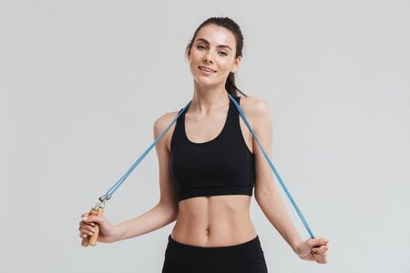 Image of a beautiful young sport fitness woman make exercises with equipment isolated over grey wall background.