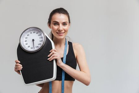 Image of a beautiful young sport fitness woman posing with scales weights isolated over grey wall background.