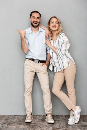 Full length image of charming european couple in casual clothing smiling and looking at camera isolated over gray background Banque d'images