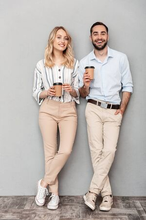 Full length photo of european couple in casual clothing holding paper cups and looking at camera isolated over gray wall