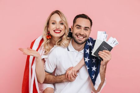 Attractive smiling young couple standing together isolated over pink background, carrying american flag, showing passport with flight tickets