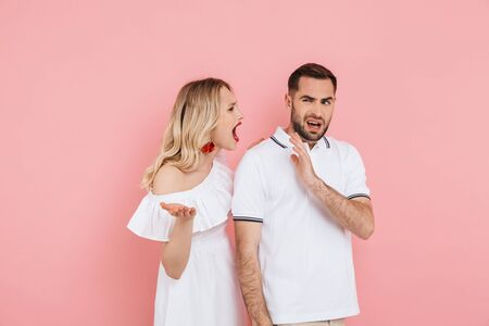 Attractive upset young couple standing together isolated over pink background, having an argument
