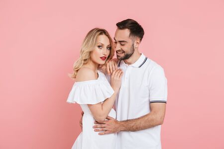 Happy beautiful couple standing isolated over pink background, embracing Reklamní fotografie