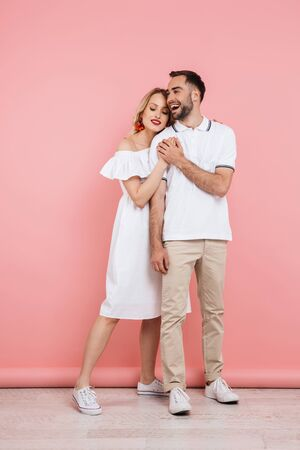 Full length of a happy beautiful couple in love standing isolated over pink background, embracing, holding hands Stock fotó