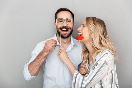 Photo closeup of pretty couple in casual clothing having fun with paper fake eyeglasses and mustaches on stick isolated over gray wall