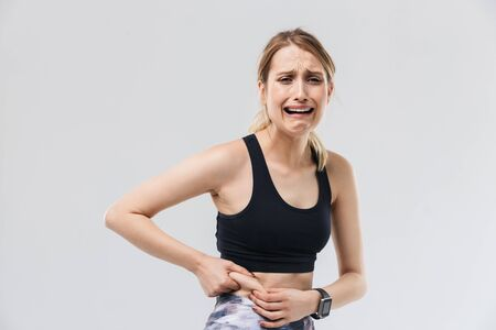 Image of upset blond woman 20s dressed in sportswear crying while touching her fat belly during workout in gym isolated over white wall