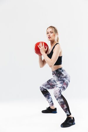 Image of active blond woman 20s dressed in sportswear working out and doing exercises with fitness ball during aerobics isolated over white wall Banco de Imagens