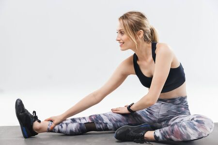 Image of joyful blond woman 20s dressed in sportswear working out and stretching her body during aerobics isolated over white wall