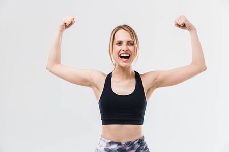Image of excited blond woman 20s dressed in sportswear working out and doing exercises with dumbbells during fitness in gym isolated over white wall