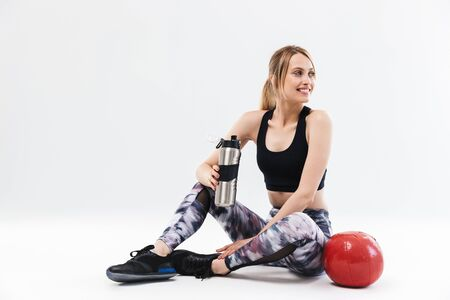 Image of european blond woman 20s dressed in sportswear working out and doing exercises with fitness ball during aerobics isolated over white wall