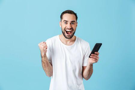 Foto di un uomo brunetta felice che indossa una maglietta di base che ride e tiene in mano uno smartphone isolato su sfondo blu