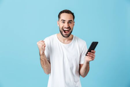 Photo of happy brunette man wearing basic t-shirt laughing and holding smartphone isolated over blue background