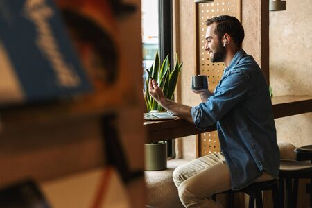 Photo of unshaven caucasian man wearing denim shirt using earpod and cellphone with cup of tea while working in cafe indoors Stock Photo