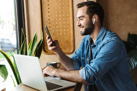 Photo of laughing caucasian man wearing denim shirt using earpod and cellphone with laptop while working in cafe indoors