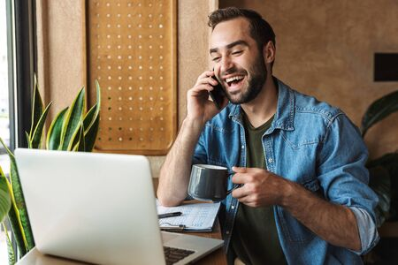 Photo of handsome laughing man wearing denim shirt talking on cellphone and drinking coffee with laptop while working in cafe indoors