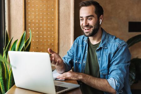 Photo of young caucasian man wearing denim shirt using earpod and laptop while working in cafe indoors Stock Photo