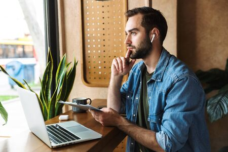 Photo of brooding caucasian man wearing denim shirt using earpod and clipboard with laptop while working in cafe indoors Stock Photo