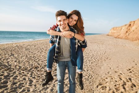 Happy young couple spending fun time at the beach, piggyback ride