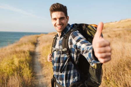 Attractive smiling young man carrying backpack, hiking, showing thumbs up