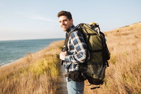 Attractive smiling young man carrying backpack, hiking