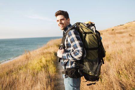 Jeune homme souriant attirant portant un sac à dos, randonnée