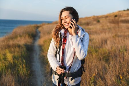 Happy young girl carrying backpack, hiking, talking mobile phone