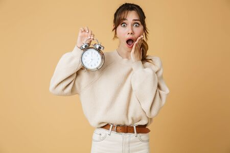 Attractive shocked young woman wearing sweater standing isolated over beige background, showing alarm clock