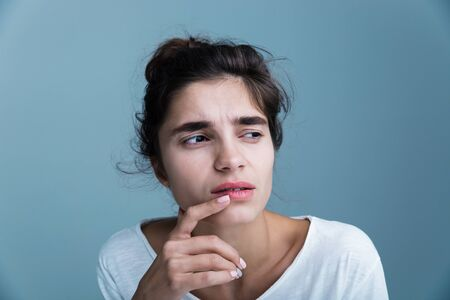 Close up portrait of a pensive unsatisfied pretty young brunette woman wearing white t-shirt standing isolated over blue background Stock Photo