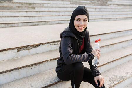 Foto di una giovane donna sorridente felice di fitness sportiva musulmana vestita con hijab e abiti scuri all'aperto in strada seduta sui gradini che tiene la bottiglia di acqua potabile. Archivio Fotografico
