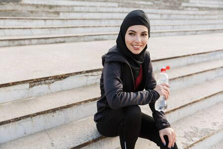 Photo of a young smiling happy muslim sports fitness woman dressed in hijab and dark clothes outdoors at the street sitting on steps drinking water holding bottle. Zdjęcie Seryjne