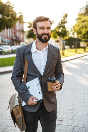 Portrait of happy adult businessman in formal suit holding takeaway coffee and paper charts while walking through city street
