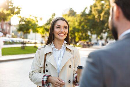 Photo d'employés de bureau heureux, homme et femme en tenue de soirée, buvant du café à emporter et se regardant tout en parlant dans la rue de la ville