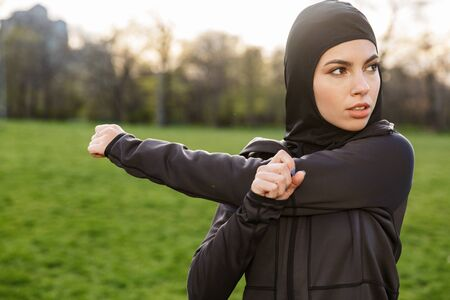 Portrait of fitness muslim woman dressed in religious black hijab stretching her arms while doing workout in green park outdoors Banque d'images