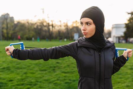 一个年轻严肃的强的强烈的穆斯林炫耀健身妇女的图象在户外穿戴在hijab和黑暗的衣裳在绿色自然公园做与设备扩展器的锻炼。