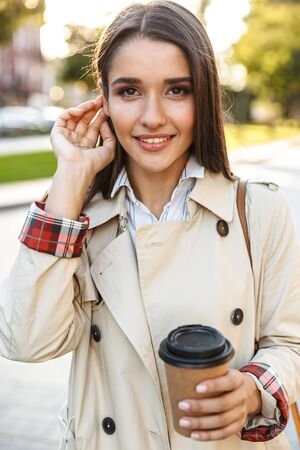 Portrait of optimistic cute woman wearing coat drinking takeaway coffee and smiling at camera while walking on city street